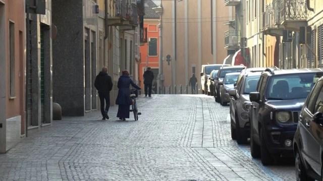 Varias personas caminan por una calle vacía en esta imagen fija sacada de un vídeo, en el pueblo de Codogno, en la provincia de Lodi, Italia, el 21 de febrero de 2020. Equipo local/REUTERS TV via REUTERS