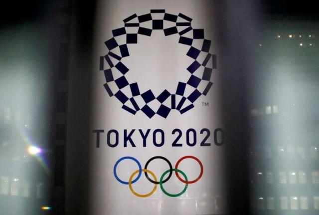 FOTO DE ARCHIVO: El logotipo de los Juegos Olímpicos de Tokio 2020 que han sido pospuestos a 2021 debido al brote de la enfermedad del coronavirus (COVID-19), visto a través de carteles, en el edificio de la Oficina del Gobierno Metropolitano de Tokio en Tokio, Japón 22 de enero de 2021. REUTERS/Issei Kato/File Photo/File Photo