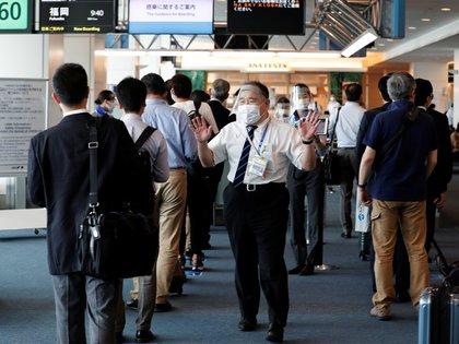 """Un miembro del personal de All Nippon Airways que lleva una máscara protectora y un protector facial pide a los pasajeros que mantengan una """"distancia social"""" mientras hacen cola para embarcar"""