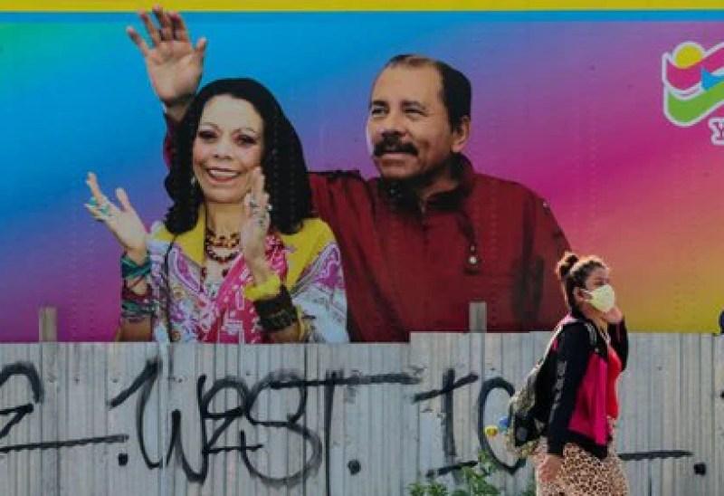 FOTO DE ARCHIVO. Una mujer que usa una mascarilla para combatir la propagación de la enfermedad por coronavirus (COVID-19) camina frente a una imagen del presidente nicaragüense Daniel Ortega y la vicepresidenta Rosario Murillo, en Managua, Nicaragua. 27 de marzo de 2020. REUTERS/Oswaldo Rivas