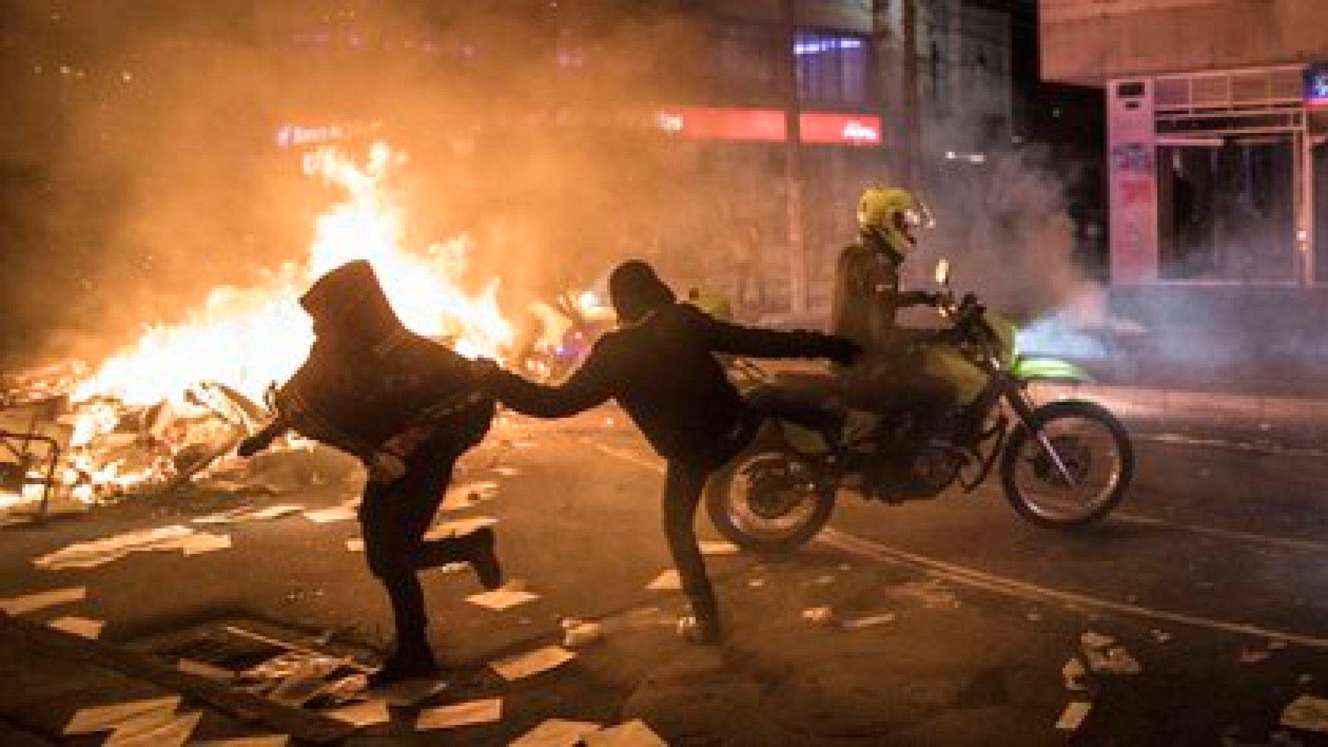 Un manifestante le pega una patada a un policía en motocicleta en Bogotá, durante la protesta nocturna (AP Photo/Ivan Valencia)