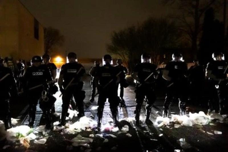 Los oficiales de policía hacen fila frente a la estación de policía del Brooklyn Center mientras la gente protesta después de que un oficial disparó y mató a un hombre negro en el Brooklyn Center, Minneapolis, Minnesota el 11 de abril de 2021.  (Photo by Kerem Yucel / AFP)