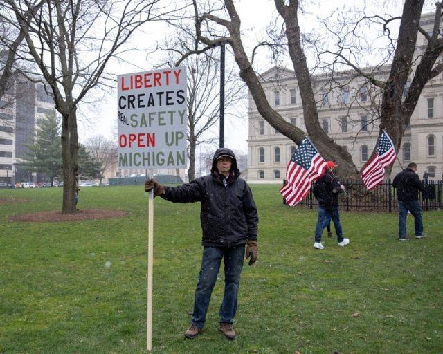 Un hombre sostiene una pancarta contra el bloqueo en Michigan REUTERS/Seth Herald