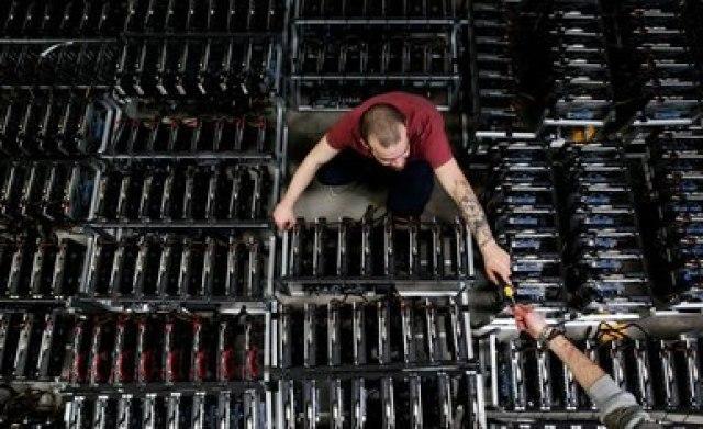 FOTO DE ARCHIVO: Empleados trabajan en computadoras de minería de bitcoin en Florencia, Italia, el 6 de abril de 2018 (REUTERS/Alessandro Bianchi)
