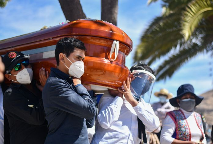 Residents of the rural community of Yura, close to the city of Arequipa, in southern Peru, participate in the burial of their mayor Angel Benavente, with an outdoor mass and an animated funeral possession on August 14, 2020, during which neighbors and musicians bade farewell to their head authority who died of COVID19. - Peru is one of worst hit countries in coronavirus-epicenter Latin America after Brazil and Mexico, with more than 25,000 reported deaths and over half a million cases. (Photo by Diego Ramos / AFP)