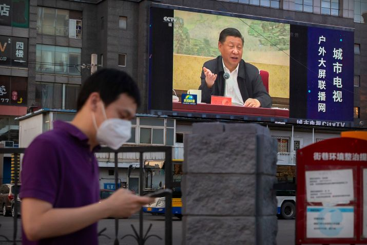 A man wearing a face mask to protect against the new coronavirus walks past a large video screen showing Chinese President Xi Jinping speaking in Beijing, Tuesday, June 30, 2020. China approved a contentious national security law that will allow authorities to crack down on subversive and secessionist activity in Hong Kong, a move many see as Beijing's boldest yet to erase the legal firewall between the semi-autonomous territory and the mainland's authoritarian Communist Party system. (AP Photo/Mark Schiefelbein)