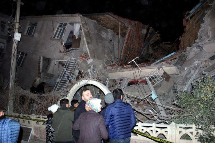 Foto del viernes de un grupo de personas paradas fuera de un edificio colapsado en la provincia de Elazig, en Turquía. Ene 24, 2020. Ihlas News Agency (IHA) via REUTERS ATENCIÓN EDITORES, ESTA IMAGEN FUE PROVISTA POR UNA TERCER PARTE. PROHIBIDA SU PUBLICACIÓN EN TURQUÍA, SU REVENTA O USO COMO ARCHIVO.