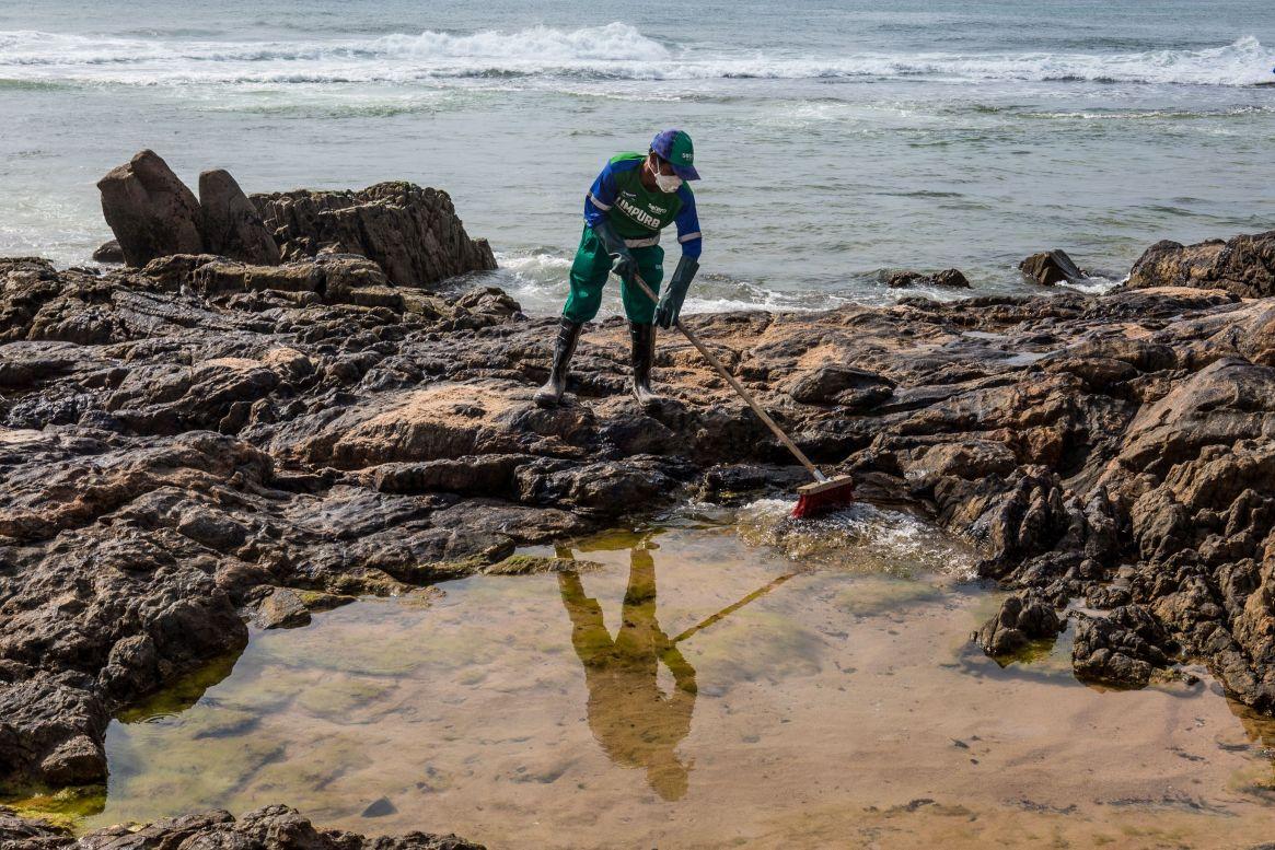 Un trabajador municipal extrae el crudo derramado en la playa de Pedra do Sal, en Salvador, estado de Bahía, Brasil, el 23 de octubre de 2019. -. (Photo by ANTONELLO VENERI / AFP)