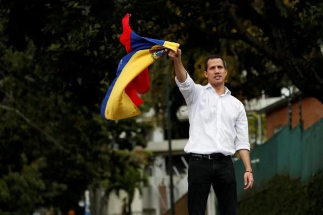 El líder de la oposición venezolana, Juan Guaidó, ondea la bandera venezolana cerca de la embajada de Bolivia en Caracas (REUTERS/Carlos García Rawlins)