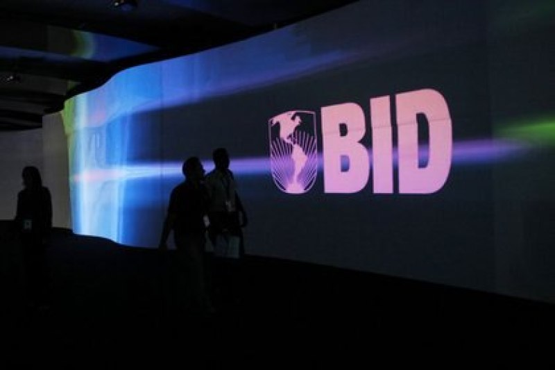 FILE PHOTO: Visitors walk past a screen with the Inter-American Development Bank (IDB) logo at the Atlapa Convention Center in Panama City.  March 13, 2013. REUTERS / Carlos Jasso
