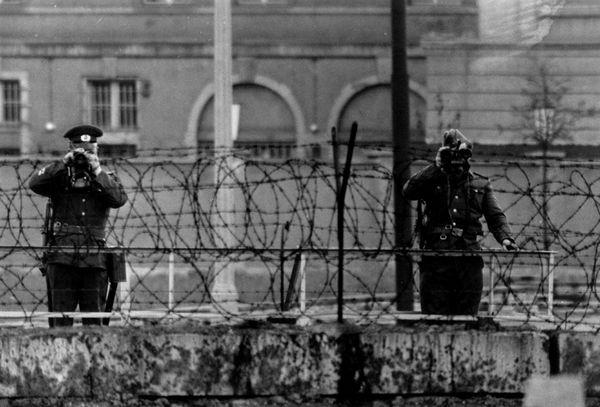 Soldados de la RDA miran a través del muro durante la visita de la reina Elizabeth y el príncipe Philip a Berlín occidental, el 29 de mayo de 1965 (Getty Images)