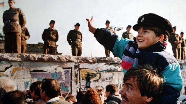 Un niño saluda a los soldados en el Muro de Berlín en frente de la Puerta de Brandenburgo el 10 de noviembre de 1989 John Tlumacki / Boston Globe 163
