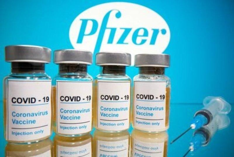 """Fotografía tomada  el 31 de octubre de 2020 en la que se ven frascos con etiquetas que dicen """"COVID-19/Vacuna contra el coronavirus/Solo inyección"""" y una jeringa médica frente al logotipo de Pfizer. (REUTERS/Dado Ruvic)"""