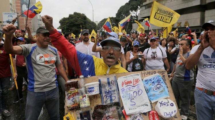 Un venezolano muestra el precio de los productos, disparados por la inflación (AP)