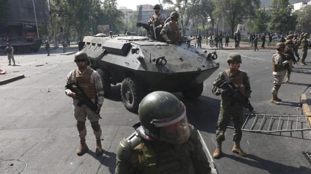 Los policías y uno de los vehículos blindados con los que recorren las calles (Reuters)