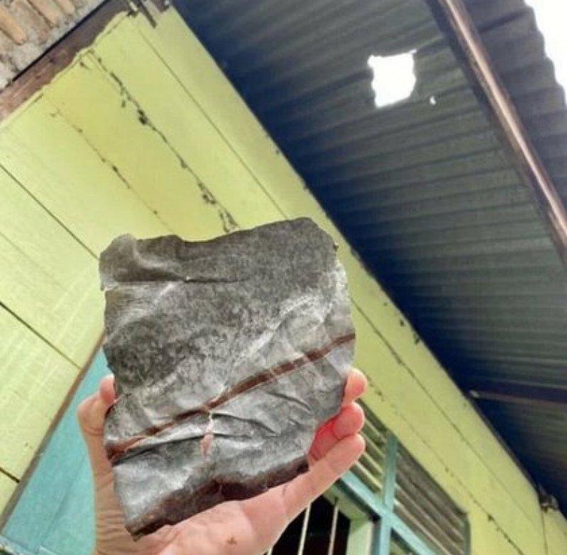 El meteorito que cayó en la casa de Josua Hutagalung y el hueco que dejó en el techo del partio.