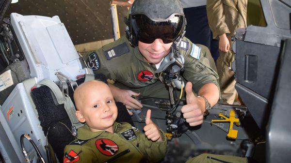 Un niño saluda junto a un piloto, sentado en un avión de combate israelí (Prensa FDI)