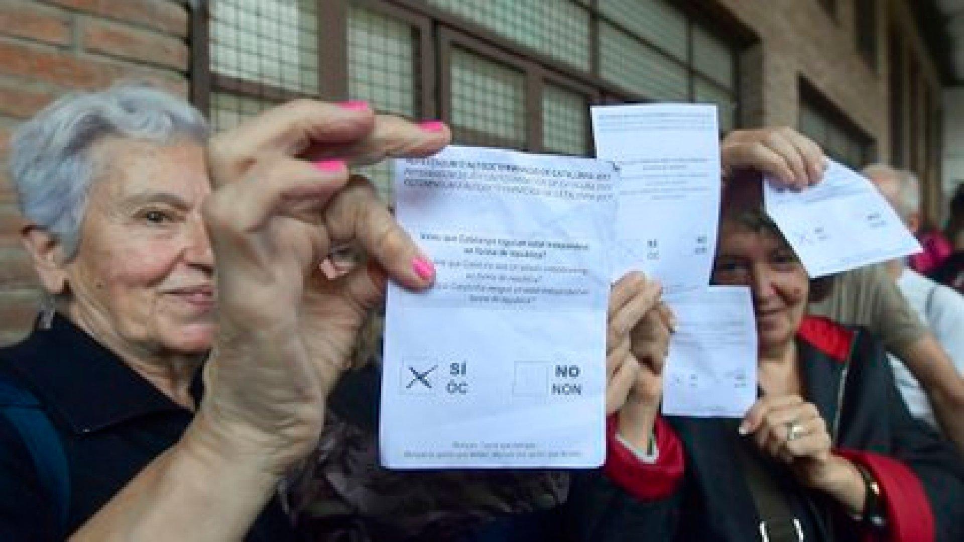 Una mujer sostiene las papeletas en un colegio electoral en Barcelona el 1 de octubre de 2017, en el día del referéndum ilegal sobre la independencia de Cataluña prohibido por Madrid (AFP PHOTO / JOSE JORDAN)