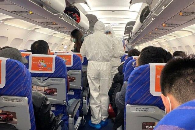 Trabajadores de salud con trajes protectores verifican la condición de un pasajero en un avión que acaba de aterrizar desde Changsha, una ciudad en una provincia vecina al centro del brote de coronavirus, en Shanghái, China. 25 de enero de 2020. REUTERS/David Stanway