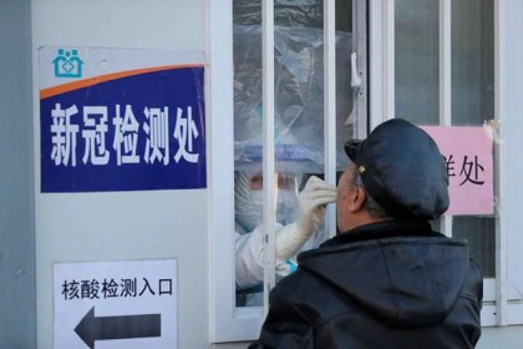 Un trabajador médico con traje protector toma un hisopo de un hombre para realizar una prueba de ácido nucleico en un hospital en Shenyang, China, 31 diciembre 2020. cnsphoto vía REUTERS