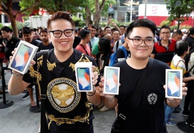 Dos jóvenes posan con los iPhone que compraron en la tienda de Signapore. REUTERS/Edgar Su