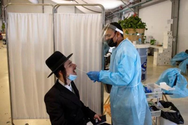 Un trabajador de la salud realiza un hisopado para detectar el coronavirus a un joven ortodoxo en el Aeropuerto Internacional Ben Gurion en Lod, cerca de Tel Aviv, Israel el 13 de abril de 2021 REUTERS / Ronen Zvulun / Foto de archivo