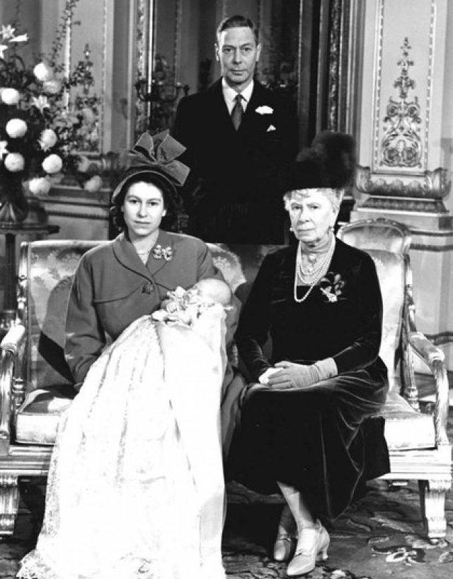 15 de diciembre de 1948, la princesa Isabel de Gran Bretaña, más tarde la reina Isabel II, sostiene a su hijo, el príncipe Carlos, en el Palacio de Buckingham, después de su bautizo. Sentada a la derecha está su abuela, la reina María, la madre de su padre, y el rey Jorge VI, al fondo