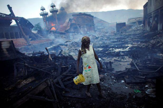 Una mujer camina cerca de un incendio en el mercado de hierro Hyppolite en Puerto Príncipe, Haití, el 29 de enero de 2010 (REUTERS/Jorge Silva)