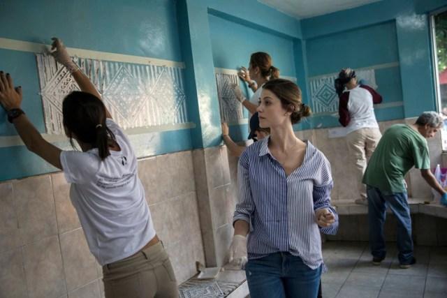 Stefanía Fernández observa el trabajo de invitados a su boda que aceptaron decorar una escuela antes de la ceremonia