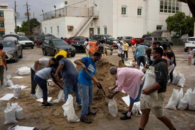 Personas llenan sacos de arena en la Iglesia de San Raimundo, proporcionados por el alcalde LaToya Cantrell y el gobierno local de Nueva Orleans, Louisiana, el 25 de agosto de 2020. REUTERS/Kathleen Flynn/Archivo Foto