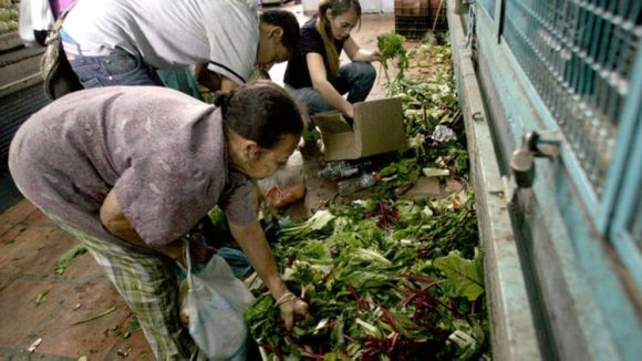 Un grupo de personas busca comida entre la basura de un mercado de Caracas.