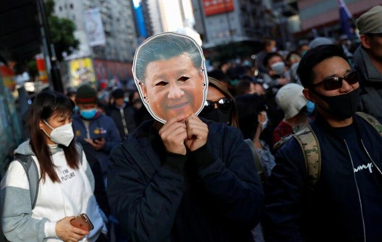 Un manifestante sostiene una máscara con la cara del presidente de China, Xi Jinping, mientras asiste a la marcha del Día de los Derechos Humanos en Hong Kong. REUTERS / Danish Siddiqui
