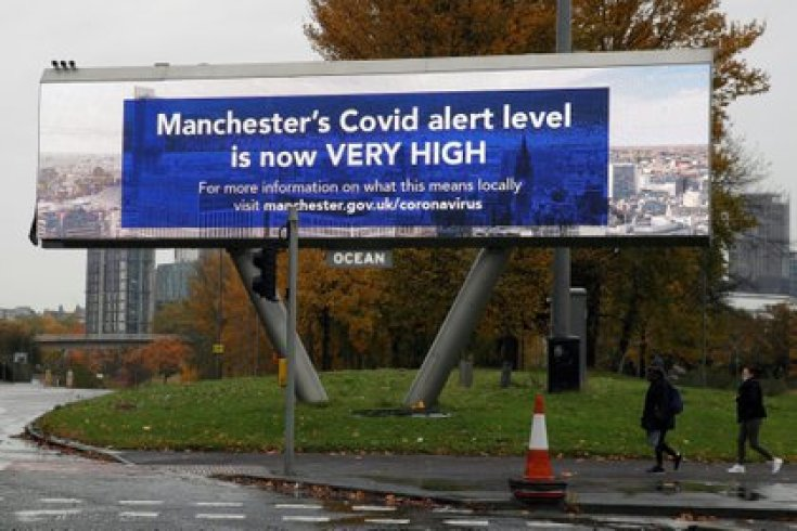 People walk past a sign about COVID-19, amid the outbreak of the coronavirus disease (COVID-19), in Manchester, Britain, October 23, 2020. REUTERS/Phil Noble