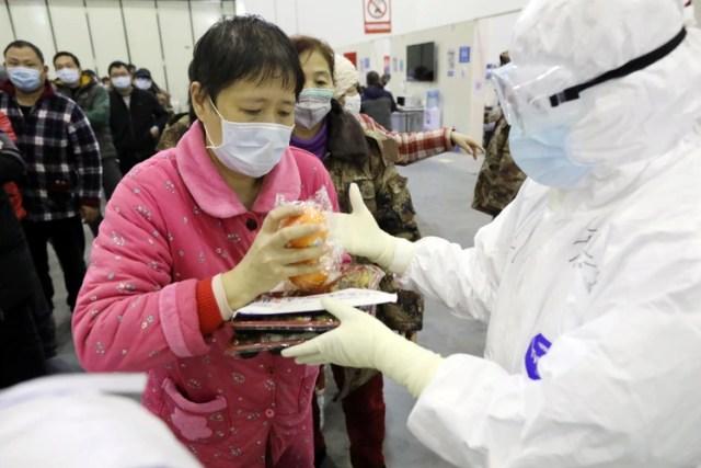 Una paciente recibe su almuerzo de un trabajador médico en el Centro de Convenciones de Wuhan Parlor que se ha convertido en un hospital improvisado (China Daily via REUTERS)