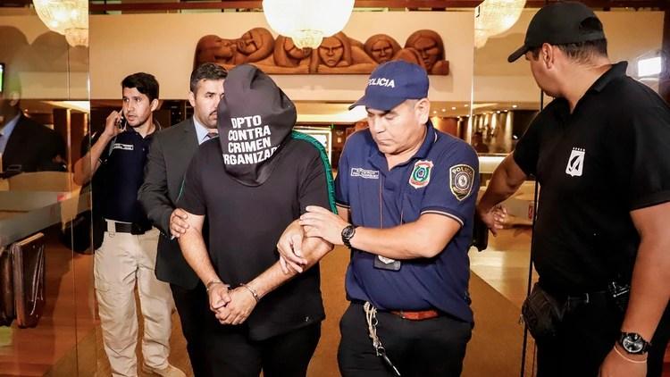 El ciudadano brasileño Wilmondes Sousa, de 45 años, sale arrestado del Hotel Yacht y Golf Club, donde Ronaldinho paso la noche bajo custodia policial (EFE)