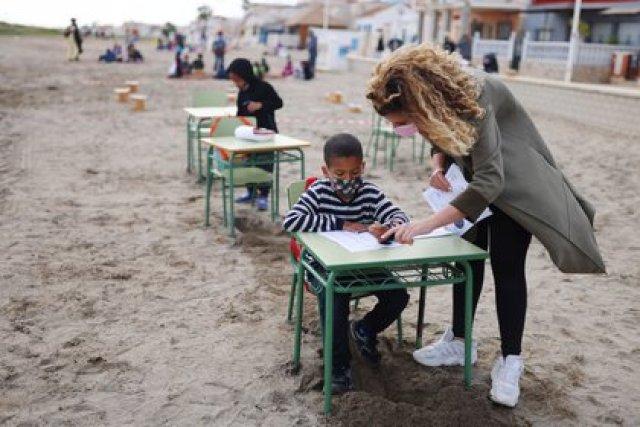 Una maestra con un estudiante durante una clase en la playa (REUTERS/Nacho Doce)