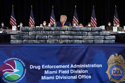 U.S. President Donald Trump sits behind stacks of confiscated drugs while attending a briefing on SOUTHCOM Enhanced Counternarcotics Operations at the U.S. Southern Command (SOUTHCOM) in Doral, Florida, U.S., July 10, 2020. REUTERS/Kevin Lamarque