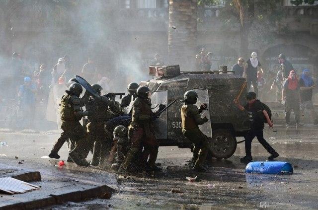 Policías se cubren detrás de un vehículo blindado (AFP)