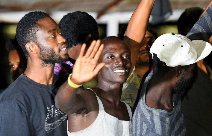 Algunos migrantes saludan tras el arribo a la isla italiana (REUTERS/Guglielmo Mangiapane)