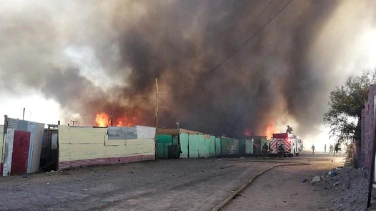 Fotografía cedida que muestra una nube de humo que se eleva entre las casas de la villa miseria, en la región chilena de Antofagasta (EFE)
