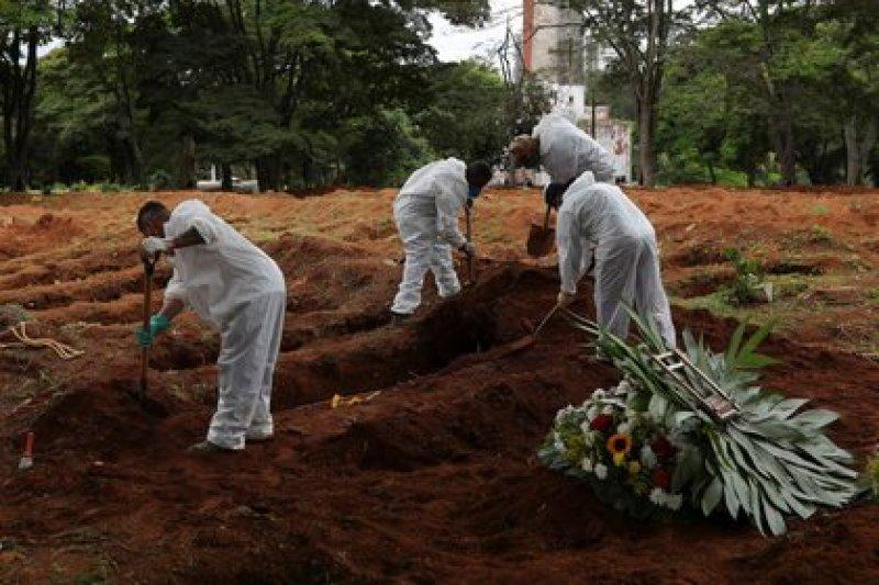 Aktenfoto von Arbeitern von einem Friedhof in Sao Paulo, die den Sarg eines Verstorbenen infolge des Coronavirus deponieren.  25. Dezember 2020. REUTERS / Amanda Perobelli