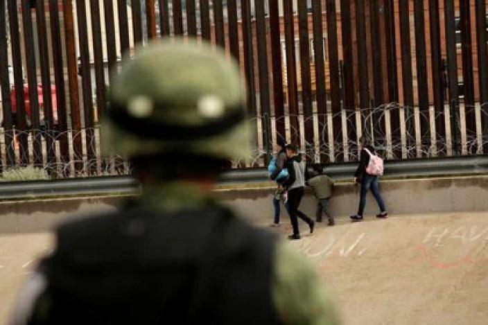 Un soldado de la Guardia Nacional observa a un grupo de migrantes después de cruzar ilegalmente a El Paso, Texas, para entregarse a agentes de la Patrulla Fronteriza (Foto: Reuters)