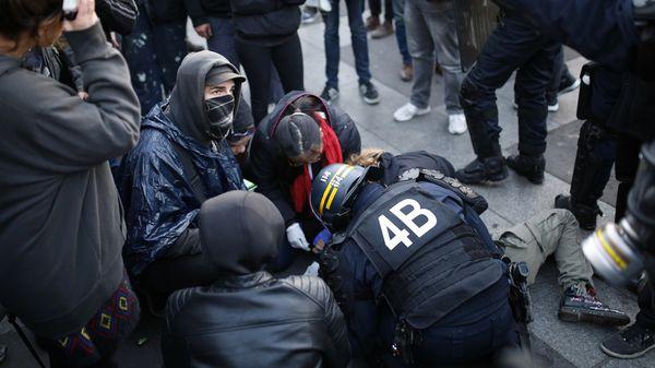 La policía atiende a un manifestantes herido durante los disturbios (AFP)