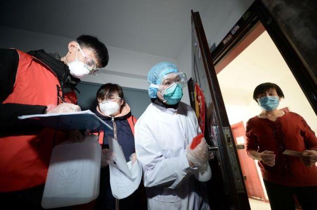 Trabajadores comunitarios y personal médico visitan a una mujer en su casa mientras realizan una búsqueda puerta a puerta para saber si hay algún nuevo caso de coronavirus en China (Reuters)