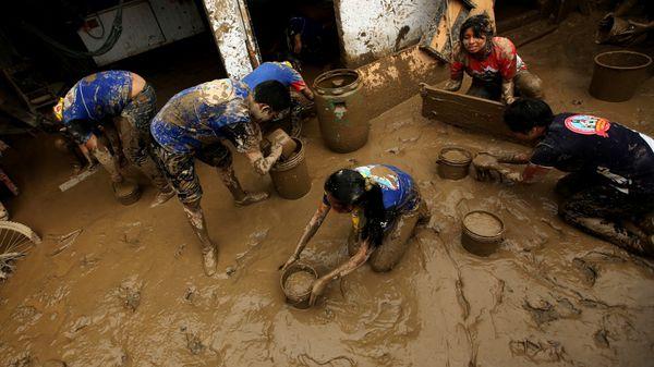 Voluntarios limpian una casa inundada tras un deslizamiento (Reuters)
