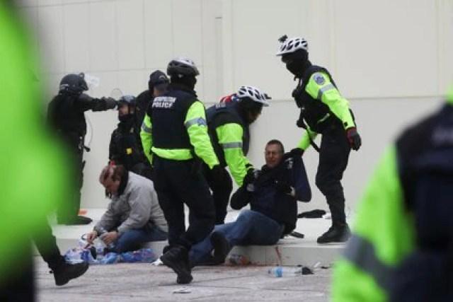 Un policía sostiene la camiseta de un hombre después de un enfrentamiento fuera del edificio del Capitolio  REUTERS/Leah Millis