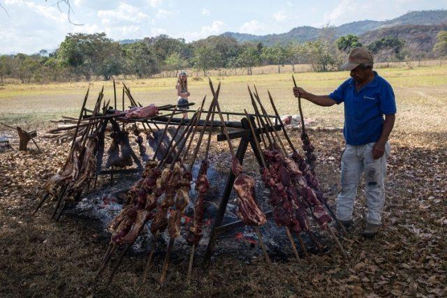 Un asador prepara carne para los asistentes a la fastuosa boda de María Fernanda Vera y Juan José Pocaterra. Los trabajadores sacrificaron una vaca y un cerdo para asarlos en una estaca, y prepararon un escenario para la fiesta digno de un concierto de rock.