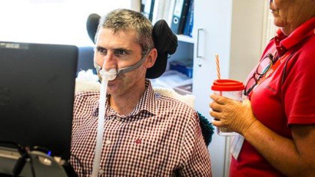 """Como no puede hablar ni escribir, Justin Yerbury se comunica con un dispositivo que sigue los movimientos de sus ojos y usa una silla de ruedas eléctrica. """"En Australia, es inusual que alguien viva por un largo período de tiempo con ventilación invasiva"""", contó a Infobae"""