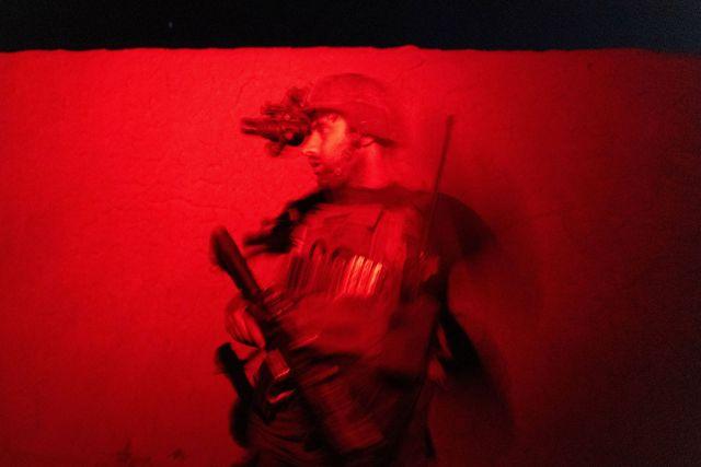 Un miembro de las Fuerzas Especiales Afganas vigila mientras otros registran una casa durante una misión de combate contra los talibanes, en la provincia de Kandahar, Afganistán, el 12 de julio de 2021.