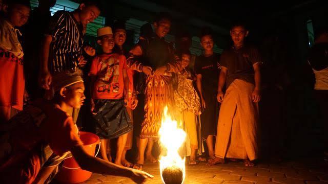 Para pemain membakar bola yang dibuat dari gulungan kain yang direndam minyak sebelum digunakan untuk bermain. (sumber: Liputan6.com)